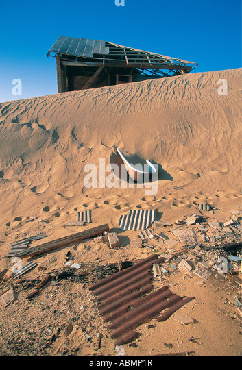 The wreckage of an abandoned house engulfed by sand dunes in the Ghost town of Kolmanskop near Luderitz Namibia - Stock Image