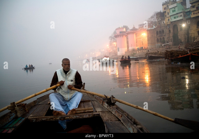 Man rowing a small boat on the River Ganges Varanasi at early morning, Uttar Pradesh, India. - Stock Image