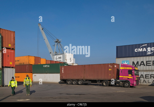 Container handling in the port of Bonn, truck with a container trailer in front of a crane, workers walking through - Stock Image