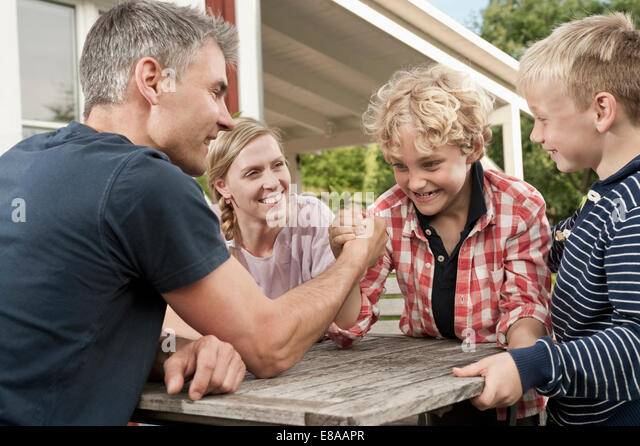 Family mother father kids boy arm wrestling - Stock Image