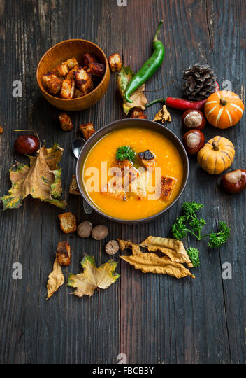 Delicious Autumn Pumpkin Soup with Croutons and Parsley and Autumn Decoration - Stock Image