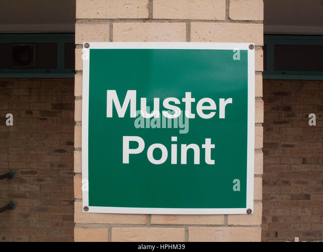 Green muster point sign on a brick pillar - Stock Image