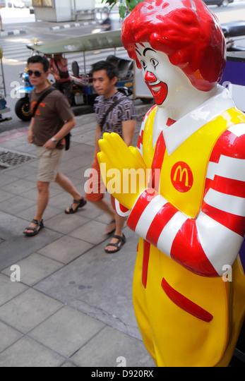 Bangkok Thailand Silom Silom Road McDonald's fast food restaurant Ronald mascot statue Thai greeting wai - Stock Image