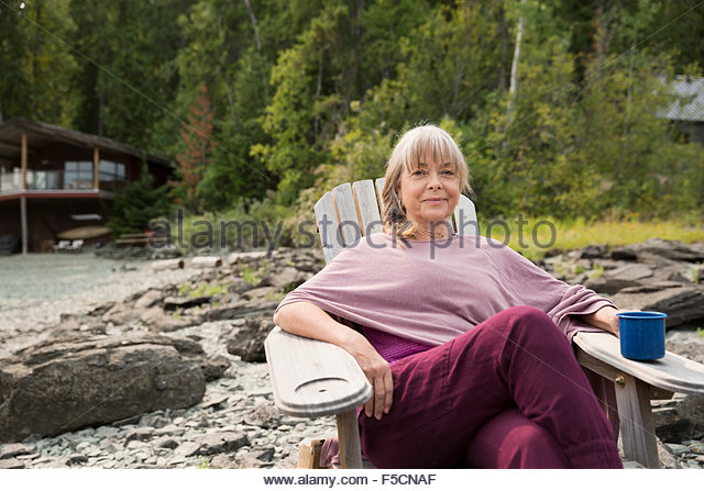 Portrait smiling woman drinking coffee outside cabin - Stock Image