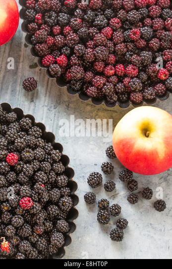 blackberries and rosy apples, for home baking a pie or crumble, agianst green marble, - Stock-Bilder