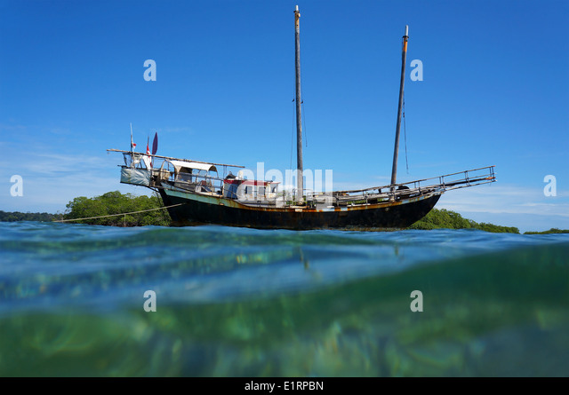 Old sailing boat stranded on a shallow reef, viewed from water surface, Caribbean sea - Stock Image