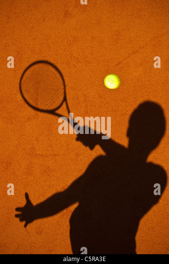 A tennis player silhouette playing the shot. - Stock Image