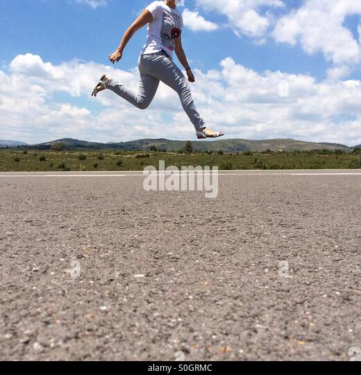 Woman jumping with no head on the picture on an empty road - Stock-Bilder