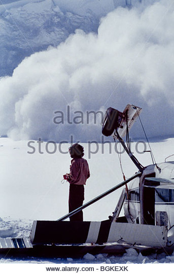 Alaska. Denali National Park. Pilot of a crashed Cessna 180 watches as avalanches rip across the upper Tokositna - Stock Image