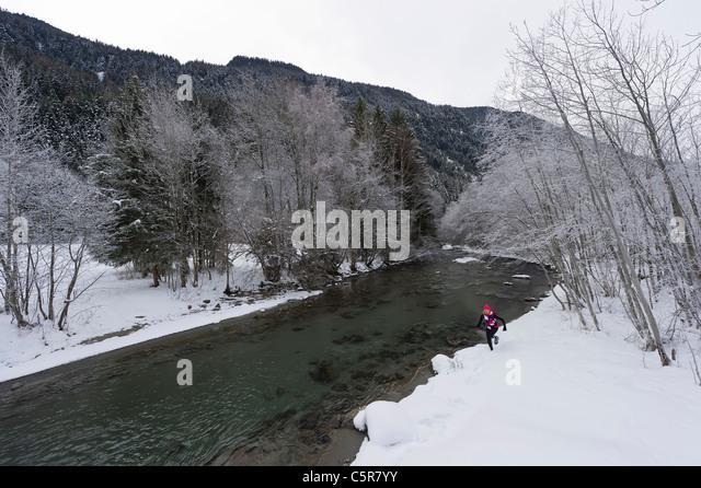 A runner jogging along a snowy river. - Stock-Bilder