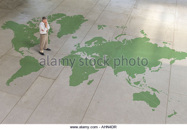 Businessman standing on world map - Stock Image