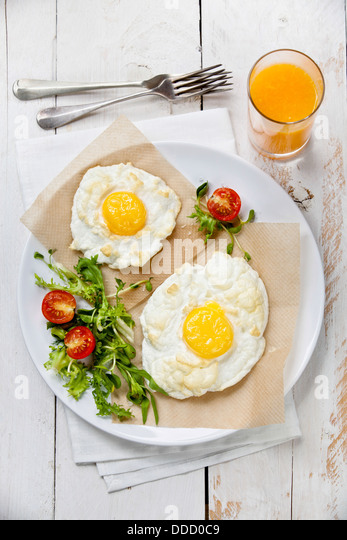 Breakfast baked egg with salad - Stock Image