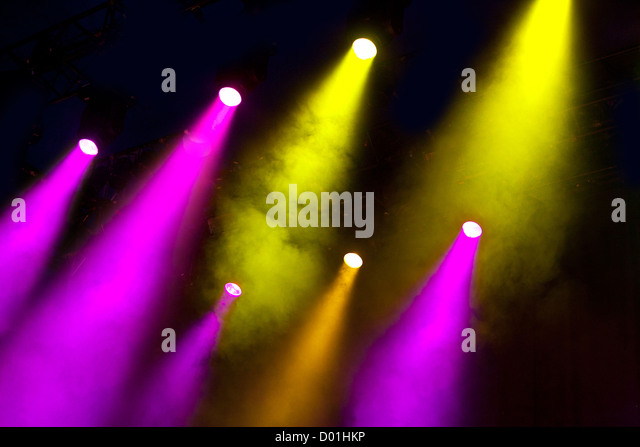 Shafts of coloured colored lighting shine through  atmospheric smoke in a dramatic way to light an empty stage - Stock Image