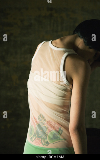Woman with tatoo on lower back, standing with head down, rear view - Stock-Bilder