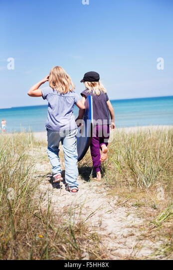 Sweden, Gotland, Faro, Two girls (8-9, 10-11) walking on beach - Stock Image