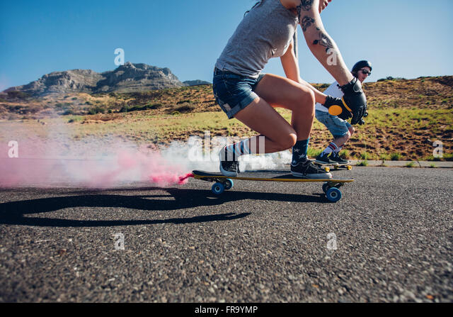 Man and woman longboarding down the road. Side view of young people practicing skating outdoors on road. - Stock Image