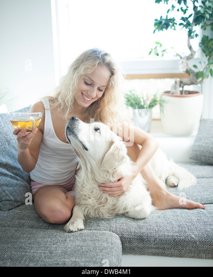 Beautiful woman holding tea cup while touching dog on sofa - Stock-Bilder