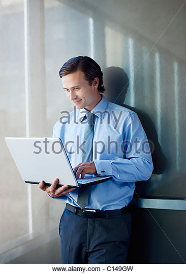 Businessman holding and typing on laptop - Stock-Bilder