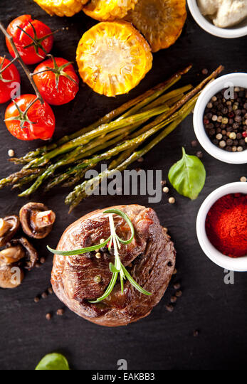 Piece of red meat steak with vegetable, herbs and spices, served on black stone surface. Shot from top view - Stock Image