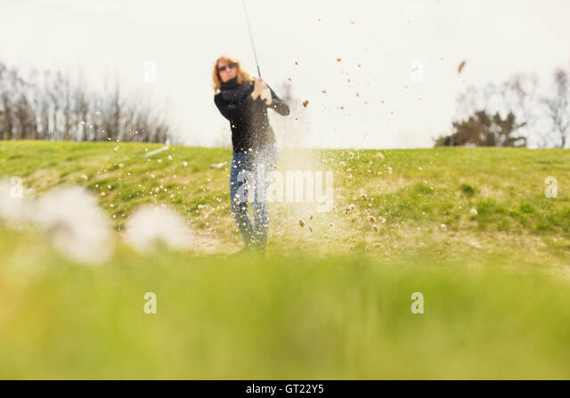 Close-up of field with woman playing golf in background at golf course - Stock-Bilder