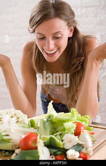 A woman looking at lots of vegetables - Stock Image