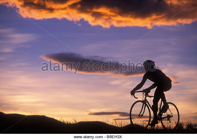 Silhouette of a road biker riding against a colorful sunset sky - Stock Image