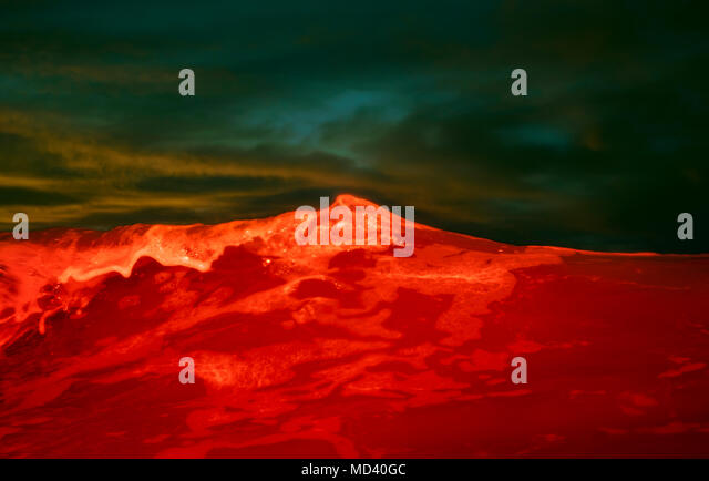 A wave coloured by red flashlight, Hook of Holland, South Holland, Netherlands - Stock Image