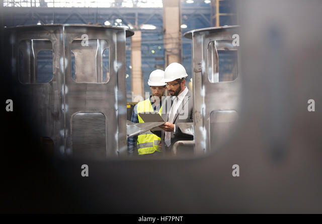 Manager and steel worker with clipboard meeting in factory - Stock Image