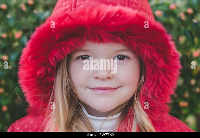 Portrait of a girl wearing a red hooded coat - Stock Image