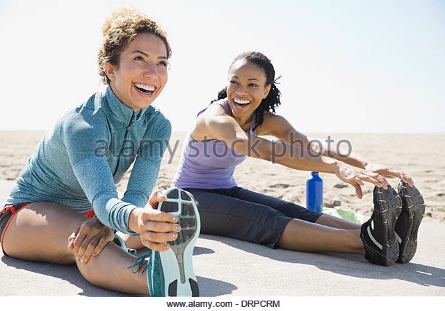 Active women stretching on beach - Stock Image