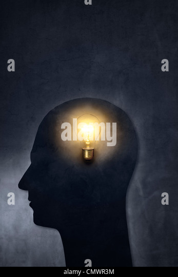 Artistic silhouette of a head with a bulb. - Stock Image