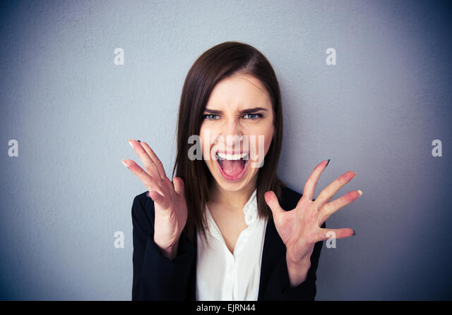 Angry woman screaming over gray background. Looking at camera - Stock Image