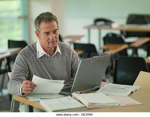 Professor using  laptop with reveiwing paperwork in classroom - Stock-Bilder