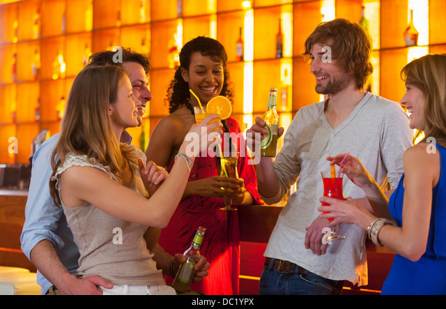 Group of friends enjoying drinks in bar - Stock Image