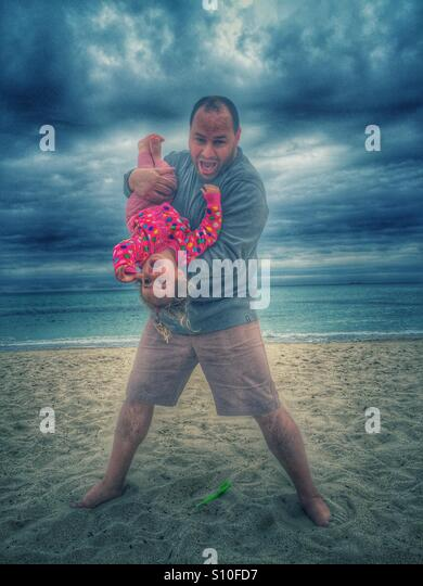 Father and baby girl playing on the beach - Stock Image