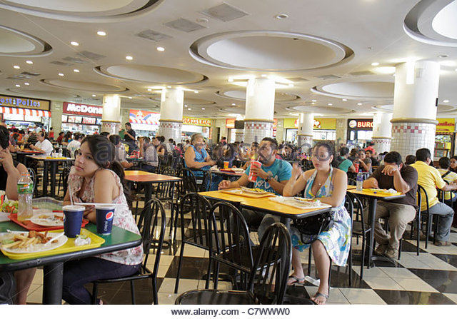 Managua Nicaragua Metrocentro shopping center centre mall food court chain restaurants crowded columns tables chair - Stock Image