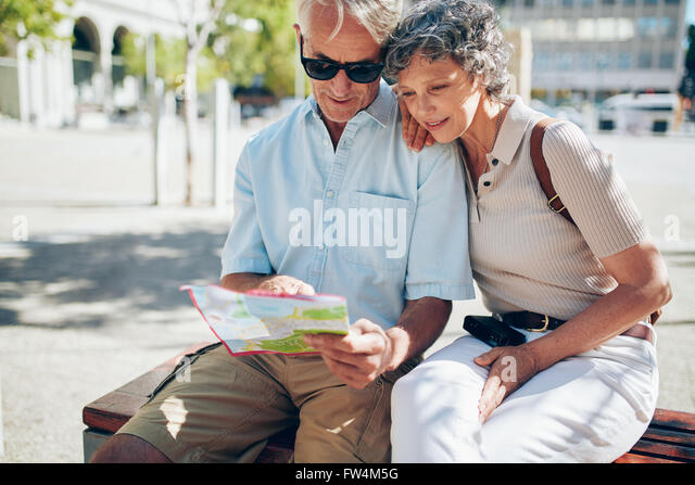 Senior couple looking for destination on a city map. Two active seniors reading a map together while sitting outdoors - Stock-Bilder