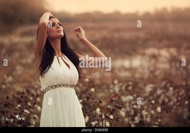 Woman in white dress standing in cotton field - Stock-Bilder