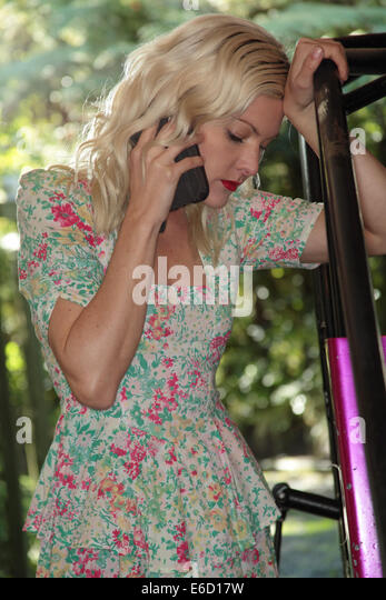 Woman on phone discussing her midget race car issues - Stock-Bilder