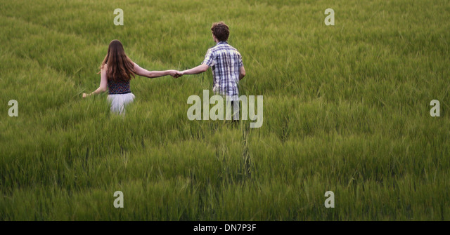 Young couple walks hand in hand through cornfield - Stock Image