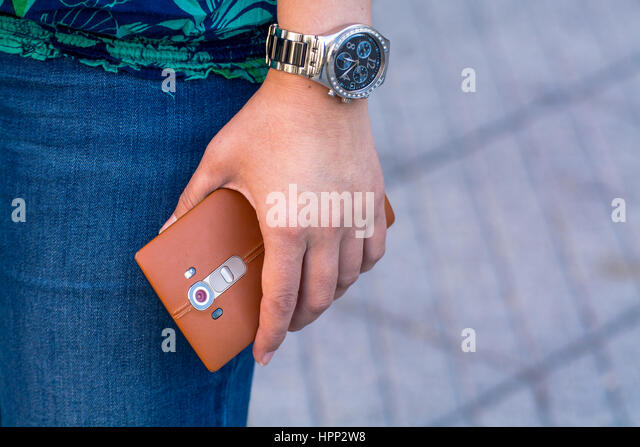 Cropped Image Of Woman Handling a Mobile Phone In The Street - Stock Image