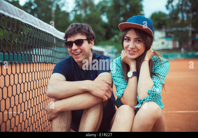 Young beautiful couple sitting on a skateboard on the tennis court - Stock Image