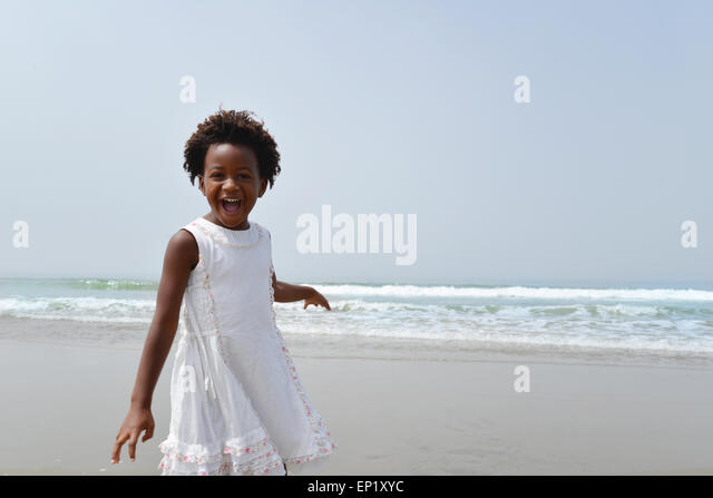 Portrait of a happy african american girl on the beach - Stock Image