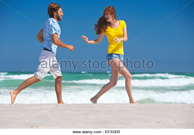 Happy couple laughing, running on sunny beach - Stock Image