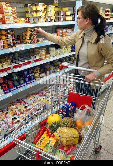 (dpa) - A young lady chooses a dairy product from the refrigerated shelf in a supermarket in Duesseldorf, Germany, - Stock Image
