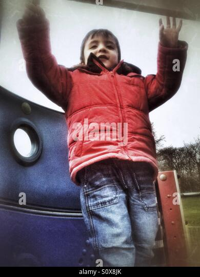 A young boy standing on top of a climbing frame. - Stock Image