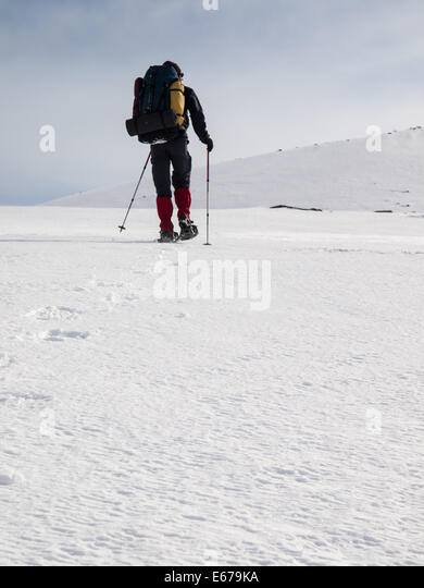 Man with heavy backpack snowshoeing in winter mountain landscape. Huldraheimen, Gausdal Westfjel, Norway - Stock Image