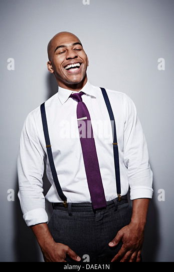 Studio portrait of businessman laughing - Stock Image