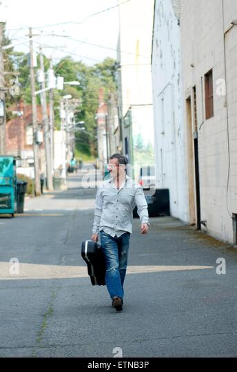 Man With Guitar Case Walking Down Alley, Port Angeles, Washington, USA - Stock Image