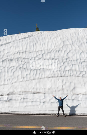 Man Smiles in Front of Tall Snow Drift - Stock Image
